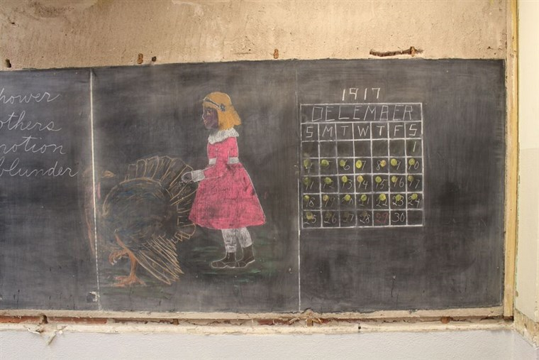 एक chalkboard featured a girl with a turkey and a calendar from 1917.