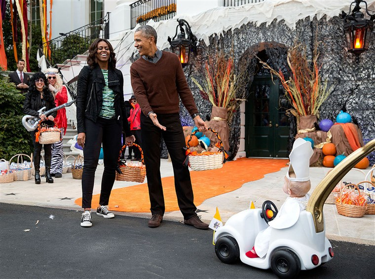 president and first lady react to a child in a pope costume and mini popemobile as they welcomed children during a Halloween event on the South Lawn of the White House on Oct. 30, 2015.