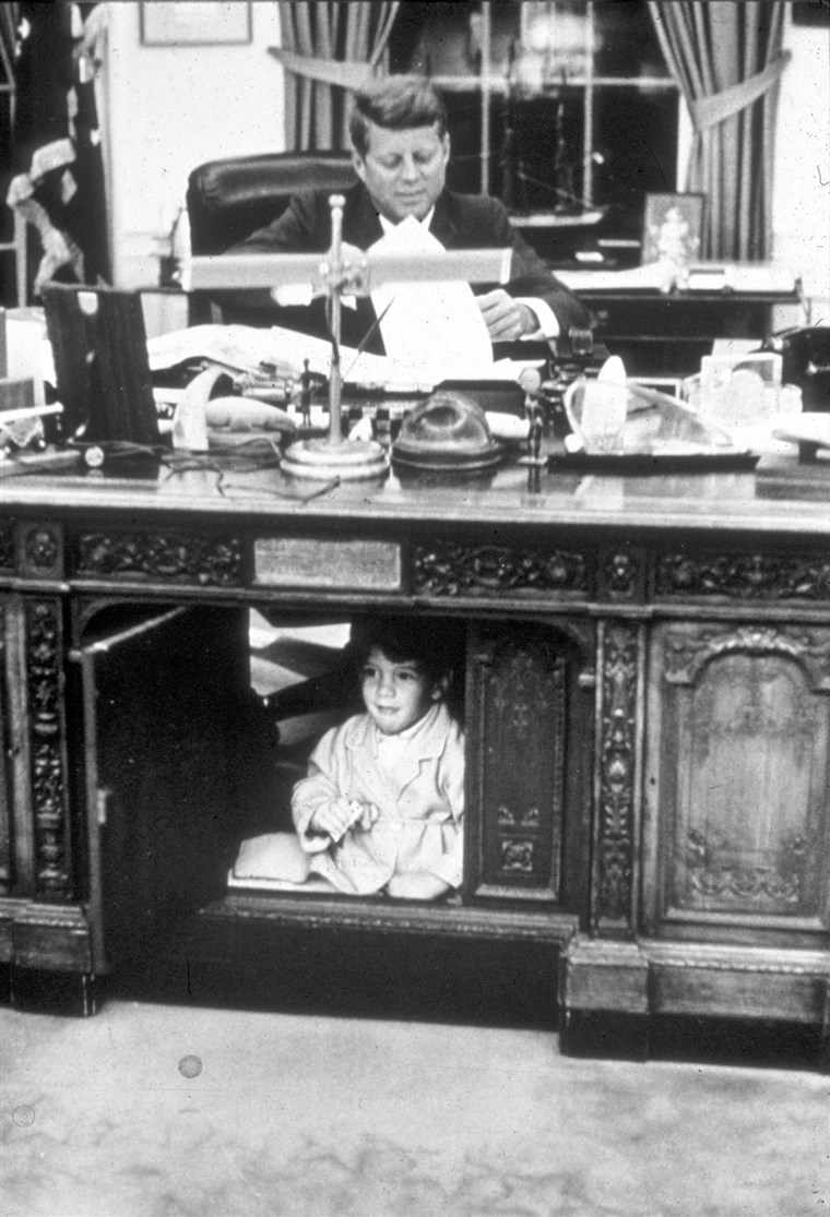 Ivan F. Kennedy Jr. hides in his father's Oval Office desk in October 1963.
