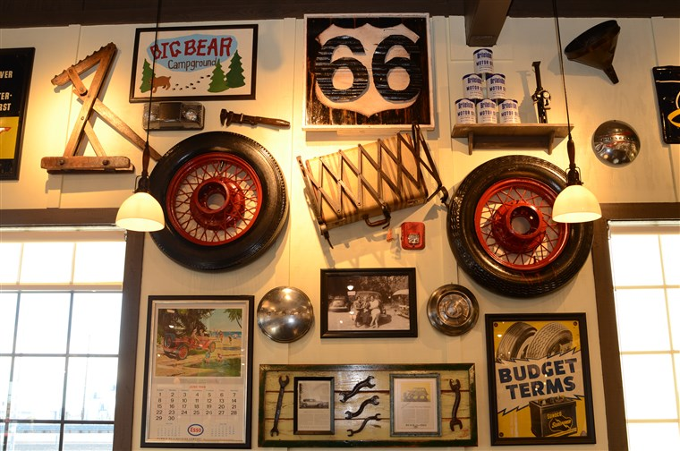 Történelmi decorations pay homage to California's Route 66, such as an antique tire, luggage rack and suitcase, old motor oil cans, and an antique Esso calendar from June 1969.