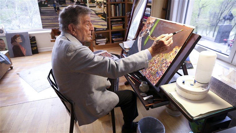 ב his New York art studio, Tony Bennett finishes a painting while sitting among several of his completed works.