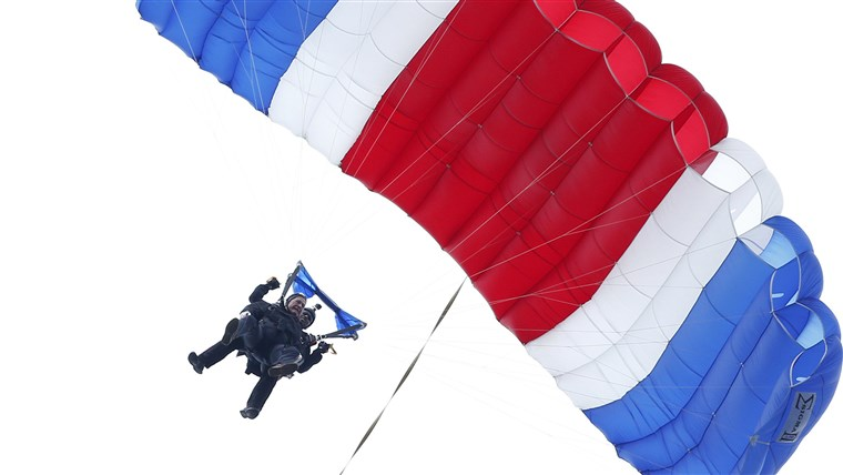 Korábbi President George H.W. Bush, strapped to Sgt. 1st Class Mike Elliott, a retired member of the Army's Golden Knights parachute team, floats to the ground during a tandem parachute jump near Bush's summer home in Kennebunkport, Maine, on Thursday in celebration of his 90th birthday.
