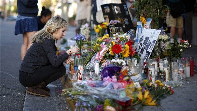 woman lights a candle at a makeshift shrine for 20-year-old UCSB student Christopher Michael-Martinez outside a deli that was one of nine crime scen...