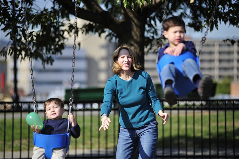 To takes a village? Writer Diana Sugg pushes her sons on the swings at the playground.