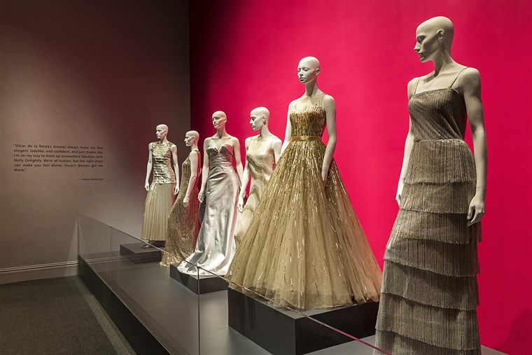שמלות lined up at the Bush Center's Oscar de la Renta exhibit.