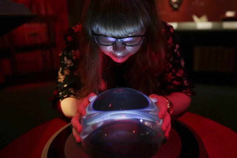 member of British Library staff poses with a crystal ball for a picture at the