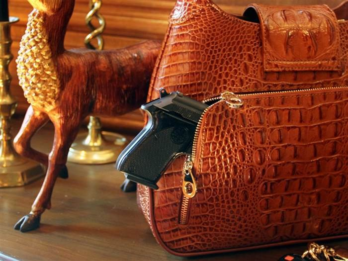 זה crocodile-print leather hobo has a discreet compartment specially designed to conceal a firearm