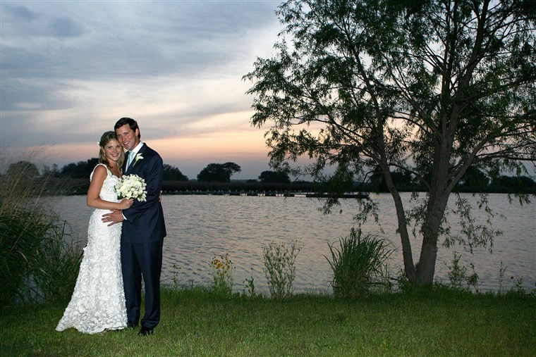 ג'נה and her husband, Henry Hager, pose along the lake at Prairie Chapel Ranch following their wedding ceremony on May 10, 2008.