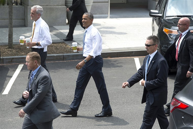 epa04246979 US President Barack Obama (C) walks down West Executive Drive on the White House campus after making a surprise visit to a Starbucks store...
