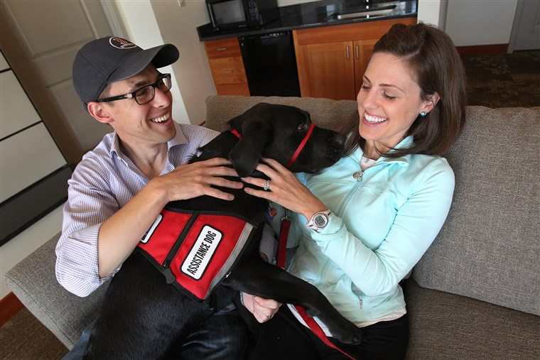 Jessica Kensky and her husband, Patrick Downes, cuddle with Rescue the dog.