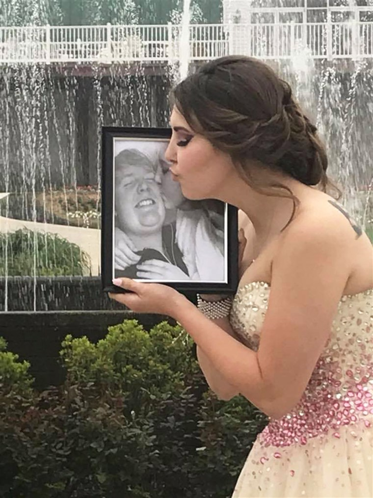 केली offers a kiss to a photo of Carter on prom night.
