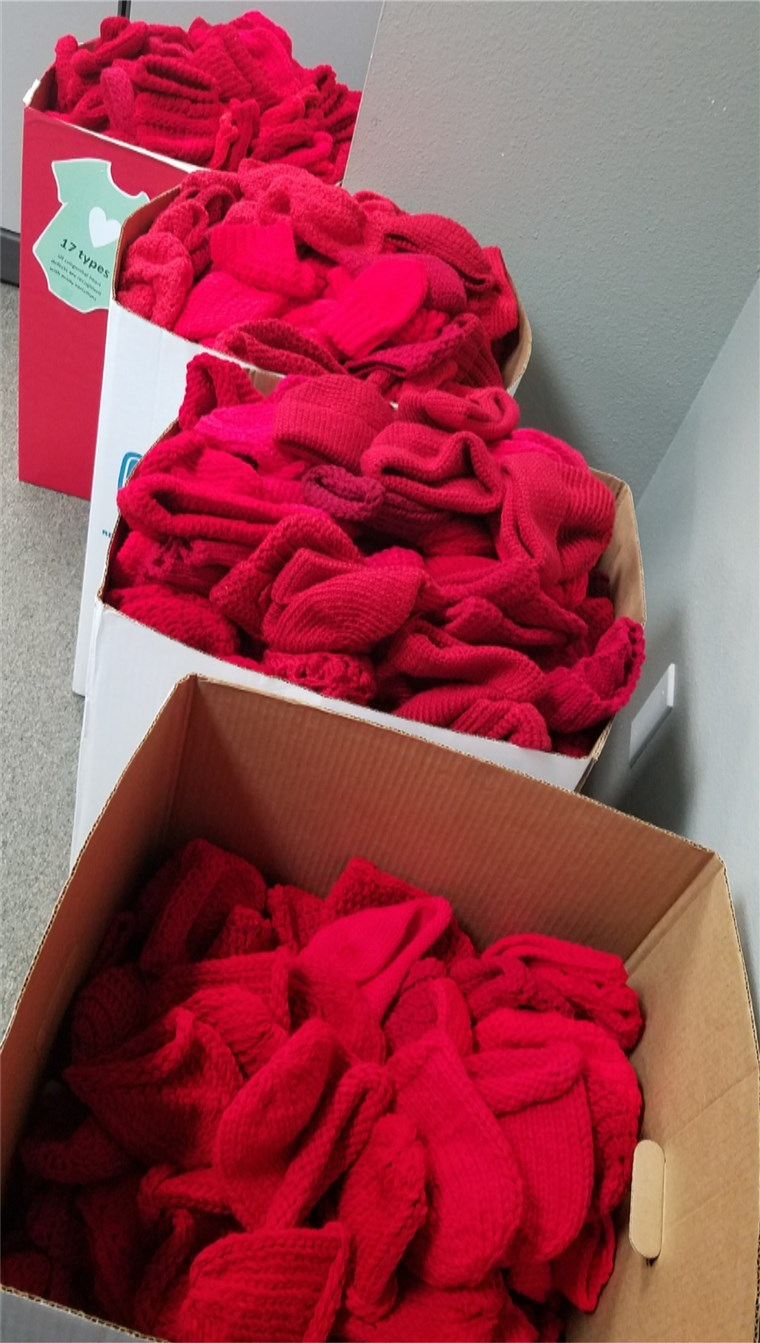 kutije of red caps knitted for babies by volunteers