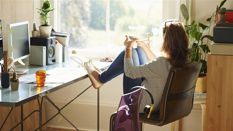 zamišljen woman looking through window with feet up on desk in sunny home office