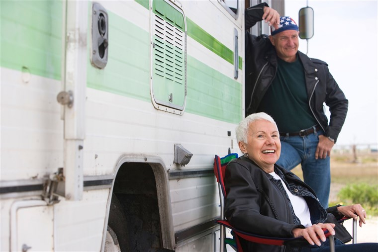 Boldog senior couple outside RV camper
